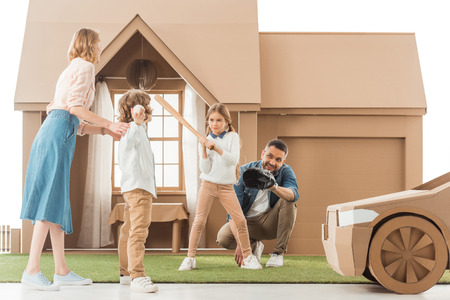 Foto de young family playing baseball together on yard of cardboard house isolated on white - Imagen libre de derechos