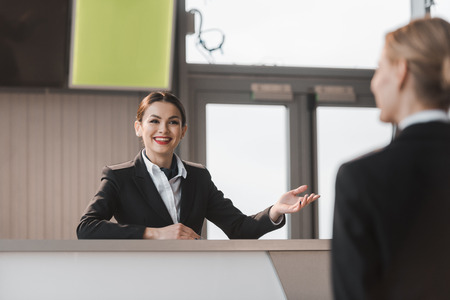 Photo pour smiling attractive airport receptionist talking to client - image libre de droit