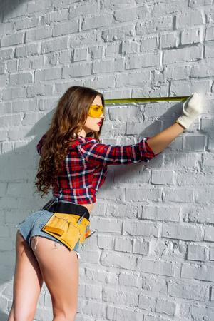 Foto de sexy girl with tool belt measuring white brick wall - Imagen libre de derechos