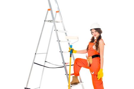 Foto de beautiful workwoman in uniform holding painting roller near ladder, isolated on white - Imagen libre de derechos