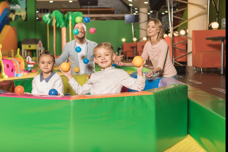 Photo for happy parents looking at cute little kids smiling at camera and playing with colorful balls in game center - Royalty Free Image