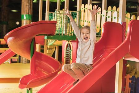 Foto de adorable happy little boy with raised hands playing on slide in game center - Imagen libre de derechos
