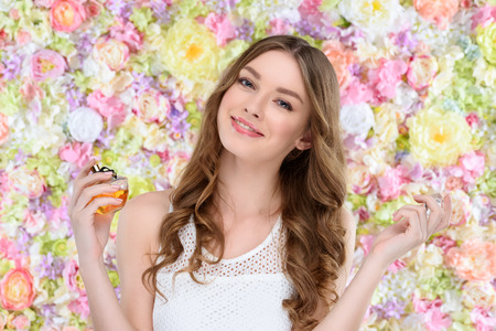 Photo pour beautiful young woman spraying perfume on floral background - image libre de droit