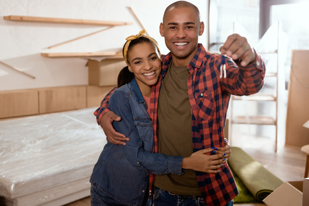 Photo pour happy african american couple holding keys in new apartment - image libre de droit