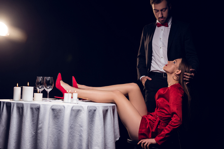 Foto de sexy woman in red dress sitting at table with her boyfriend - Imagen libre de derechos