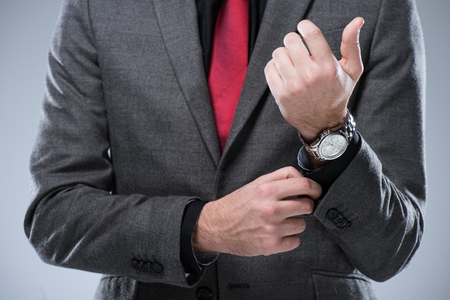 Foto de Midsection of businessman in formal suit adjusting button on sleeve, isolated on gray - Imagen libre de derechos