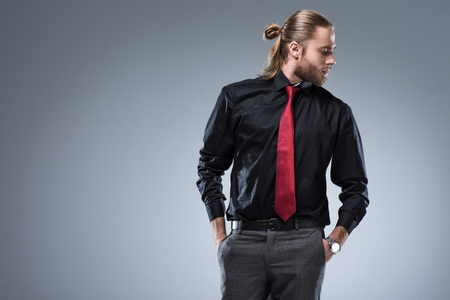 Foto de Young  bearded man in black shirt with red tie looking away, isolated on gray - Imagen libre de derechos