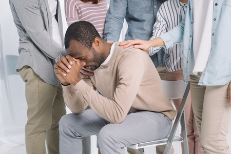 Photo pour cropped shot of people supporting depressed middle aged african american man during group therapy - image libre de droit