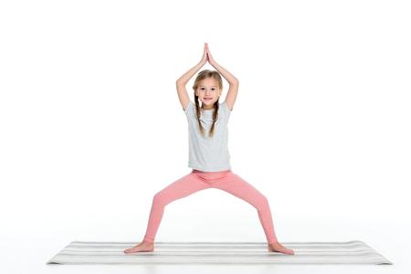 Photo pour kid practicing yoga on yoga mat isolated on white - image libre de droit