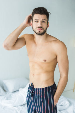 Photo for handsome shirtless man standing in bedroom in the morning - Royalty Free Image