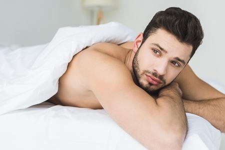 handsome bearded man lying on white bed