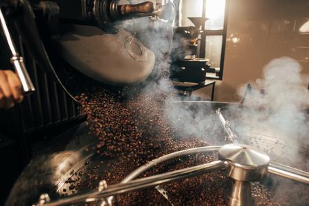 Foto de close up view of coffee beans roasting in machine - Imagen libre de derechos