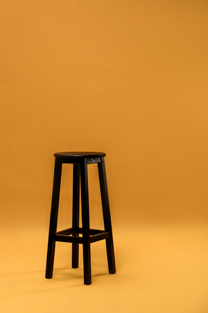 Photo for Dark wooden bar stool on orange background - Royalty Free Image