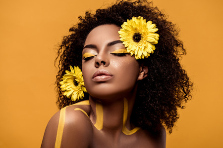 Foto de Young sensual african american woman with artistic make-up and gerbera in hair isolated on orange background - Imagen libre de derechos