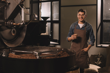 smiling coffee roster with cup of coffee having break during work