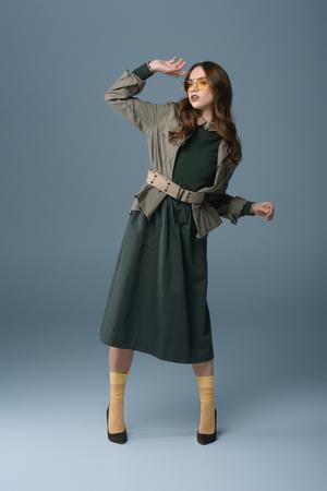 Foto de attractive stylish girl posing in trendy autumn outfit, isolated on grey - Imagen libre de derechos