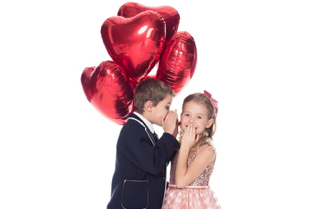 Foto de stylish little boy holding heart shaped balloons and whispering to smiling beautiful little girl isolated on white - Imagen libre de derechos