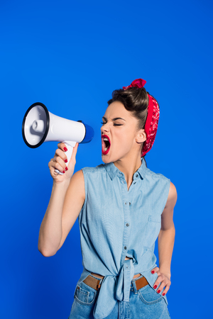 Foto per fashionable young woman in pin up style clothing with loudspeaker isolated on blue - Immagine Royalty Free