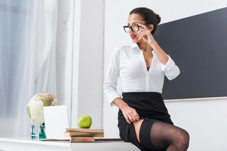 Photo pour young sexy teacher in stockings sitting on desk at classroom - image libre de droit