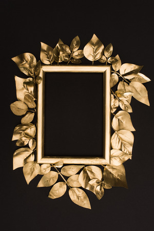 Foto de top view of golden photo frame and leaves isolated on black - Imagen libre de derechos