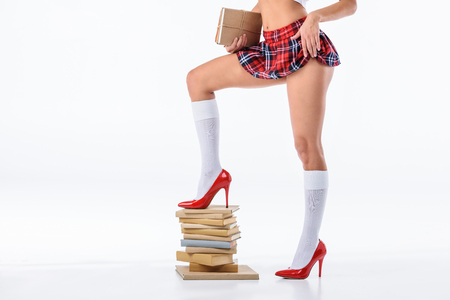 Photo for cropped shot of sexy schoolgirl standing on stack of books isolated on white - Royalty Free Image