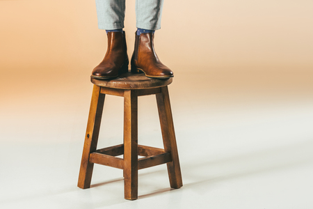 Foto de cropped shot of man standing on wooden chair - Imagen libre de derechos