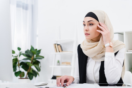 Foto de pensive arabic businesswoman sitting at workplace in office - Imagen libre de derechos