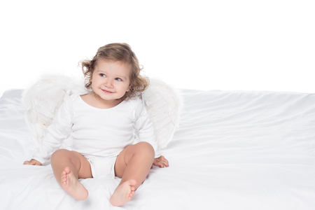 Foto de adorable smiling baby with wings sitting on bed, isolated on white - Imagen libre de derechos
