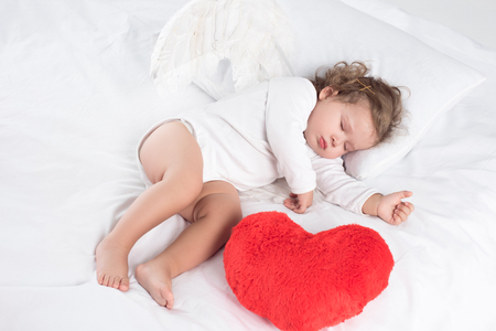 Photo for little baby with sleeping on bed with heart, isolated on white - Royalty Free Image
