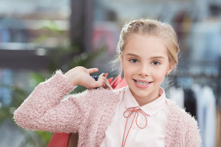 Photo for happy child looking at camera and holding paper bags in hand - Royalty Free Image