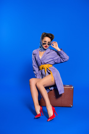 Foto de fashionable young woman in retro clothing with suitcase isolated on blue - Imagen libre de derechos