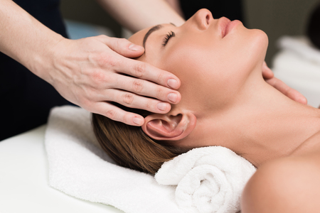 Photo pour young woman relaxing and having head massage in spa salon - image libre de droit