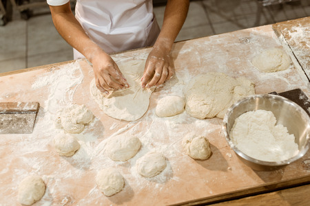 cropped shot of female baker kneading dough for pastry