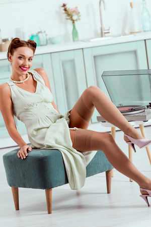 Foto de Smiling pin up girl sitting on ottoman near recor player - Imagen libre de derechos