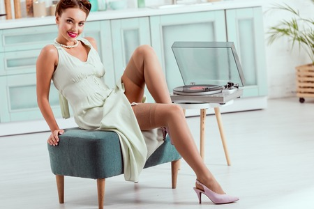 Foto de Flirty pin up girl sitting on ottoman near record player - Imagen libre de derechos