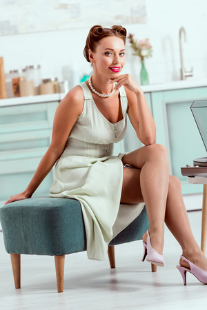 Photo pour Beautiful pin up girl sitting on ottoman and looking at camera - image libre de droit