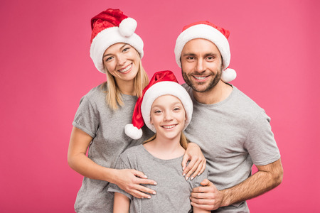 Photo pour portrait of smiling family with daughter in santa hats, isolated on pink - image libre de droit