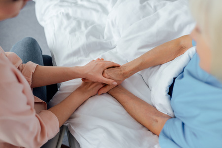 Foto de cropped view of senior woman and daughter holding hands in hospital - Imagen libre de derechos