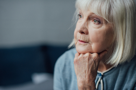 Foto de portrait of thoughtful senior woman propping chin with hand at home - Imagen libre de derechos