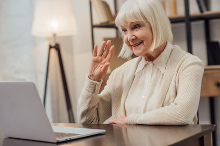 Foto de smiling senior woman sitting at computer desk and waving while having video call at home - Imagen libre de derechos