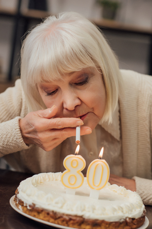 Foto de senior woman lighting up cigarette from burning candles on birthday cake at home - Imagen libre de derechos