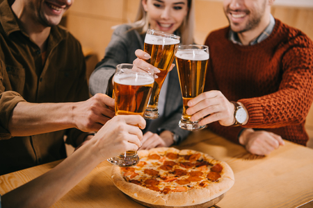 Foto de cropped view of friends clinking beer near pizza in bar - Imagen libre de derechos