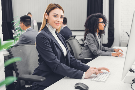Photo pour beautiful young businesswoman using desktop computer and smiling at camera in office - image libre de droit