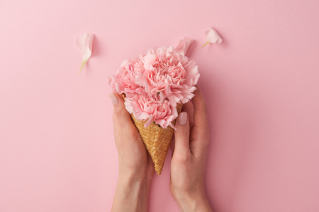 Photo pour cropped shot of woman holding wafer cone with beautiful tender flowers isolated on pink - image libre de droit