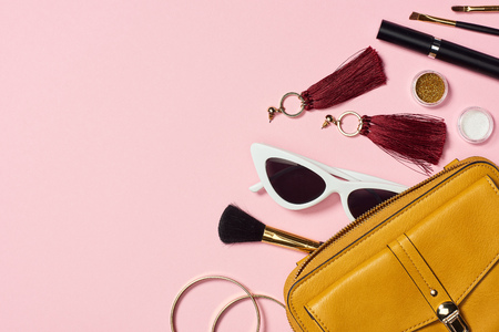 Photo pour Top view of bracelets, earrings, sunglasses, mascara, cosmetic brushes, eyeshadow and bag on pink background - image libre de droit