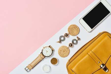 Photo pour Top view of earrings, eyeshadow, watch, smartphone and yellow bag - image libre de droit