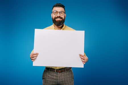 Foto de cheerful man holding blank placard isolated on blue - Imagen libre de derechos