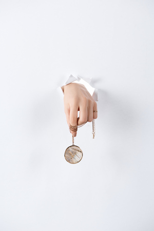 Photo pour cropped image of woman holding hand with beautiful luxury round locket with marble through white paper - image libre de droit