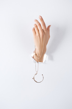 Photo pour cropped image of woman holding hand with beautiful luxury necklace through white paper - image libre de droit