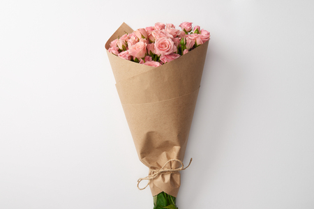 Foto de bouquet of beautiful pink roses wrapped in craft paper on grey - Imagen libre de derechos